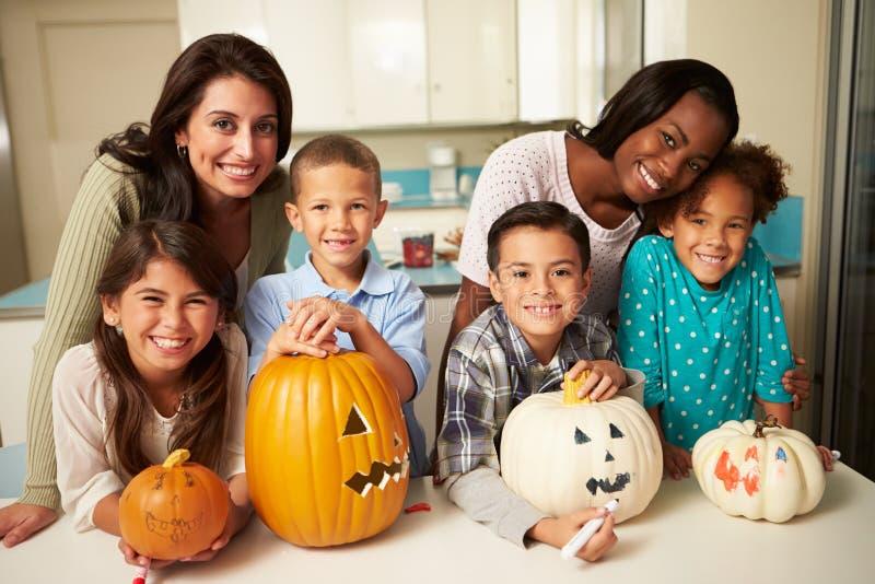 Mödrar och barn som gör allhelgonaaftonlyktor fotografering för bildbyråer