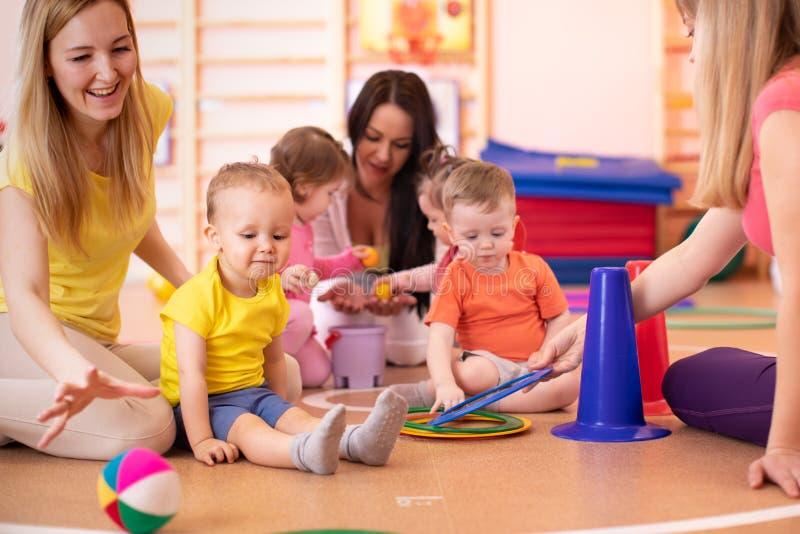 Mödrar och deras barn tillsammans i idrottshall Behandla som ett barn att spela med sportive utrustning royaltyfri foto