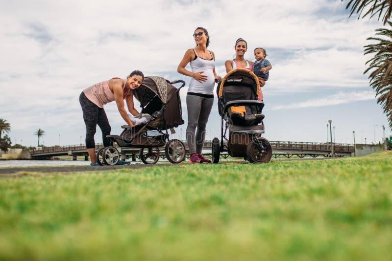 Mödrar på en morgon går med deras ungar behandla som ett barn in prams royaltyfria foton