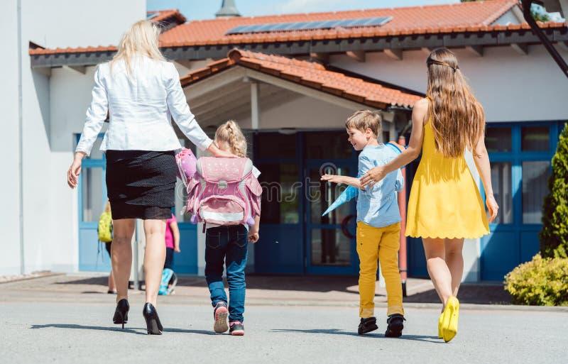 Mödrar som kommer med ungarna till skola i morgonen arkivbild