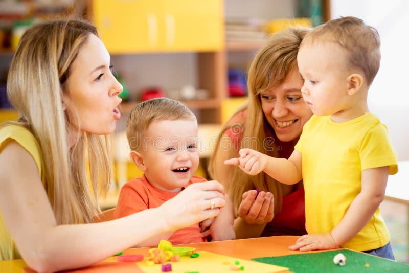 Mödrar undervisar barn att arbeta med färgrik lekleraleksaker royaltyfria bilder