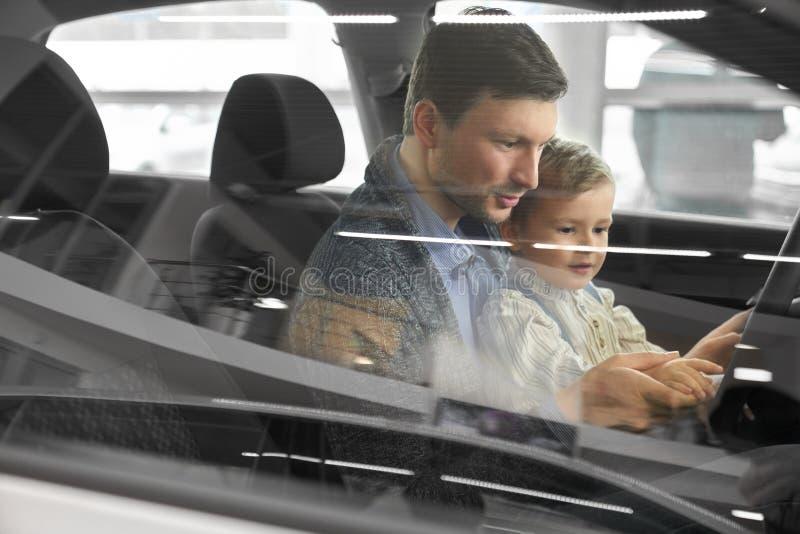 Möglicher Käufer des Autoprüfungsautos mit Sohn stockbilder
