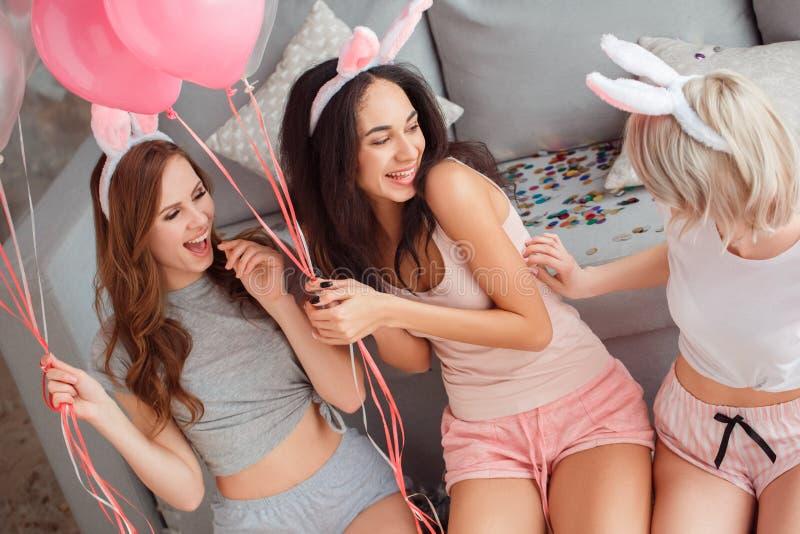 Möhippa Unga kvinnor i kaninöron hemma som sitter tillsammans nära soffan som spelar med gladlynt närbild för ballonger royaltyfri foto