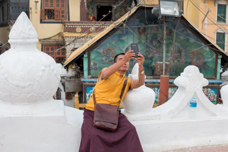 Mönch, der Fotos mit Telefon macht stockbild