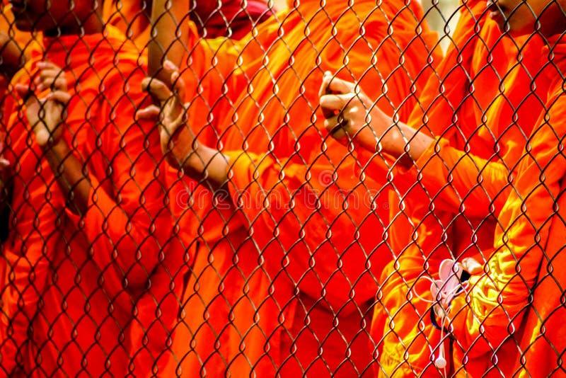 Mönche hinter einem Zaun lizenzfreie stockbilder