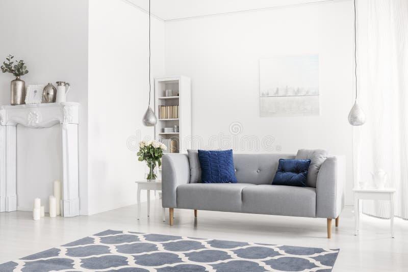 Mönstrad blå matta framme av den gråa soffan i den vita lägenhetinre med blommor och lampor Verkligt foto fotografering för bildbyråer