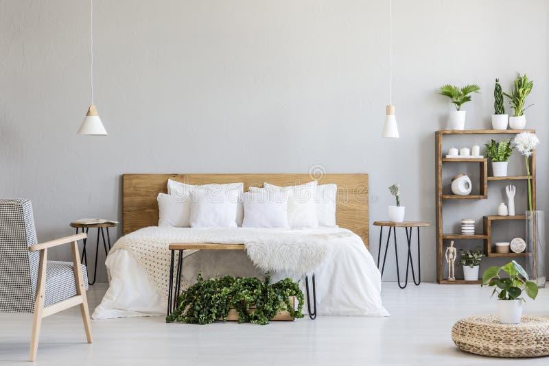 Mönstrad fåtölj nära vit träsäng i grå sovruminre med puffen och växter Verkligt foto royaltyfri bild