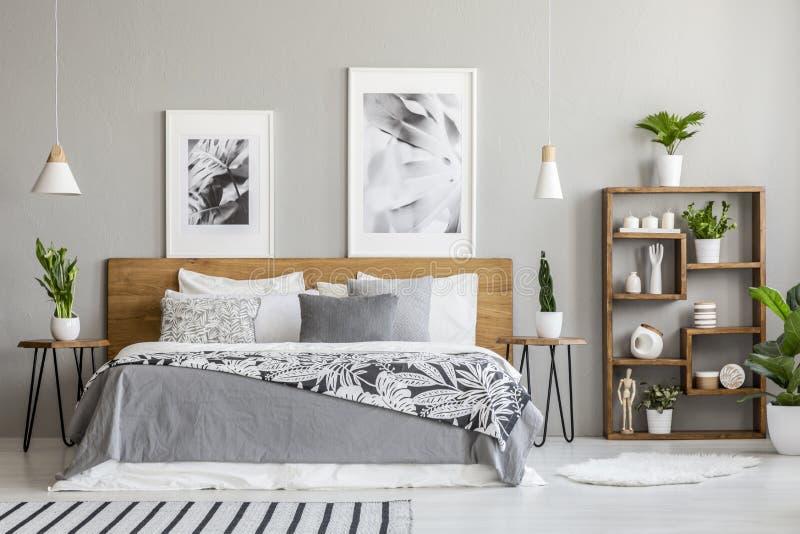 Mönstrad filt på träsäng mellan tabeller med växter i sovruminre med affischer Verkligt foto royaltyfri foto
