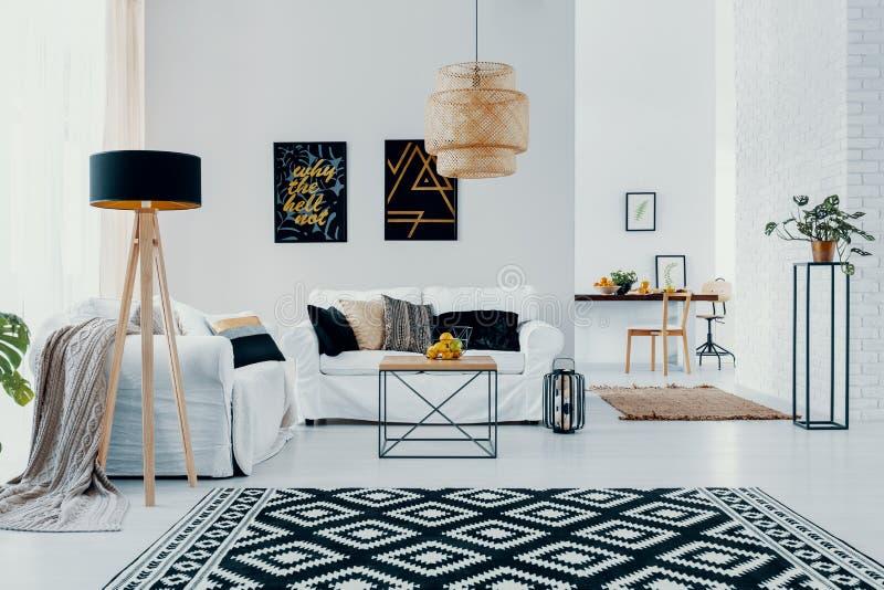 Mönstrad matta och lampa i den vita vardagsruminre med affischer ovanför soffan med kuddar Verkligt foto royaltyfria bilder