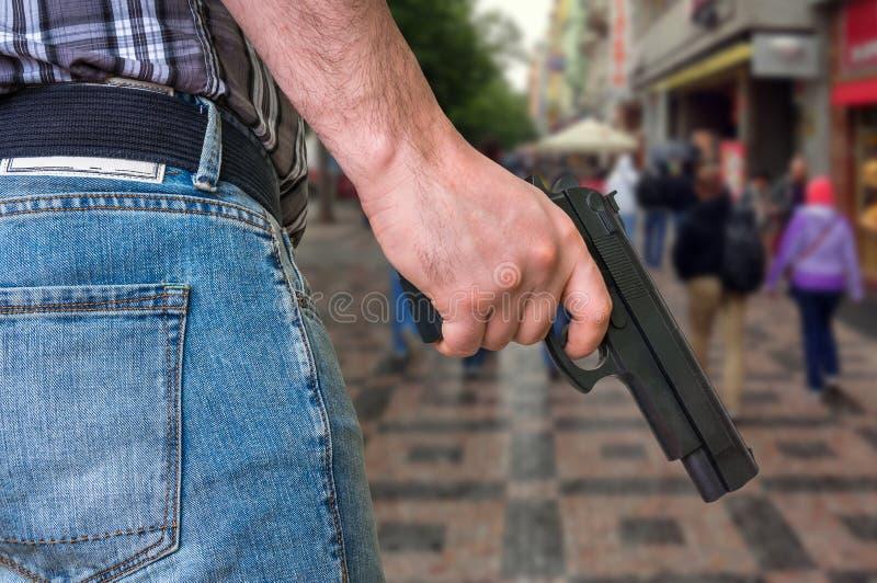 Mördare med pistolen och folkmassan av folk på gatan fotografering för bildbyråer