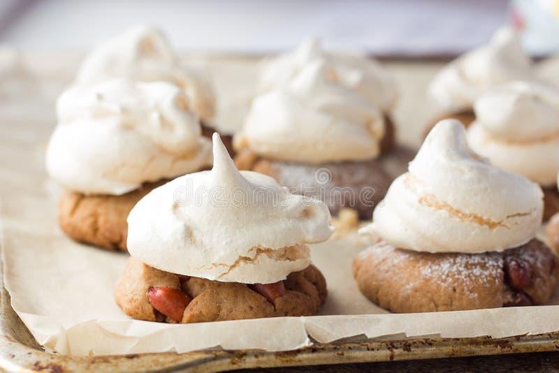 Mördegskakakakor med marängar på matlagningpapper arkivbild