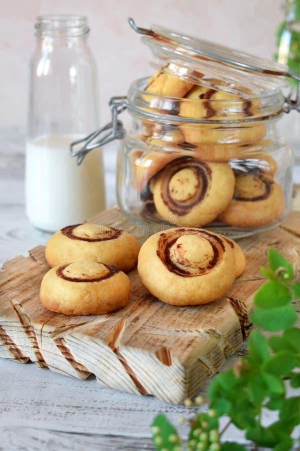 Mördegskakan champignon-formade kakor på ett träbräde och i en exponeringsglaskrus royaltyfria bilder