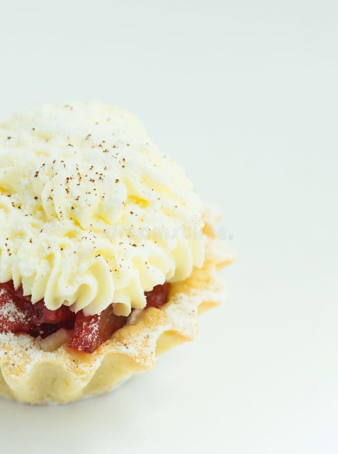 MördegskakaTartlet med jordgubbedriftstopp och piskad Buttercream glasyr på kaka på vit bakgrund europeisk bakelse Feriebakning royaltyfria foton