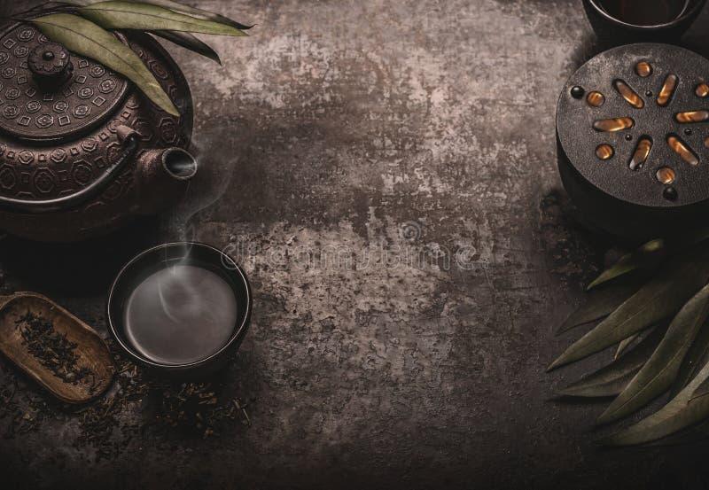 Mörk asiatisk tebakgrund med den svarta järntekannan och att råna av grönt te kopieringsutrymme för din design Autentisk tappning arkivbild