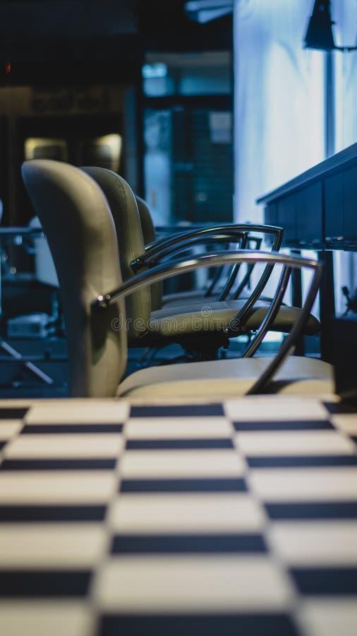 Mörk atmosfär med sikt av tänt rum med stolar royaltyfri bild