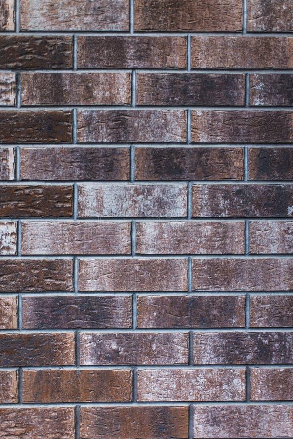 Mörk bakgrund för brountegelstenvägg, textur vertikalt royaltyfri foto
