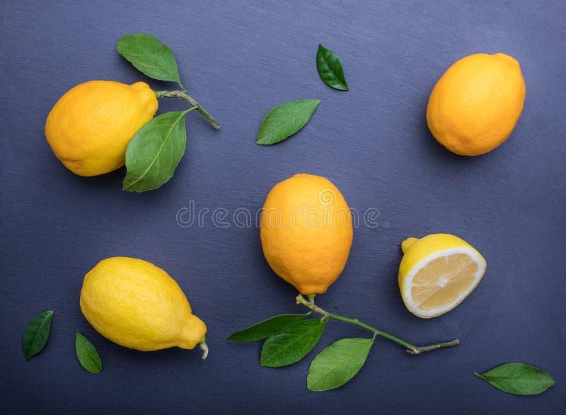 Mörk bakgrund med citroner på stentabellen royaltyfria bilder