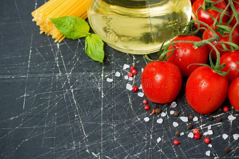 Mörk bakgrund med körsbärsröda tomater, pasta, ny basilika royaltyfria bilder
