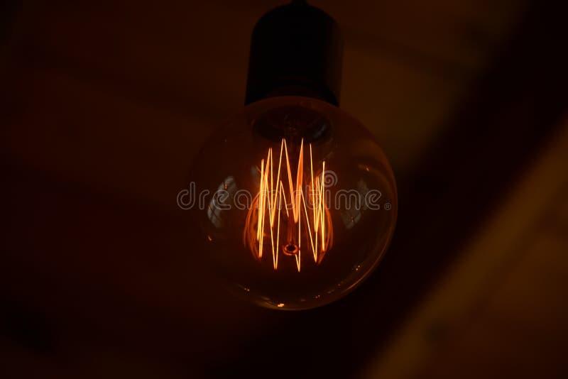 Mörk bakgrund med retro-kulan Edison Vägg-legitimationshandlingar med den märkes- lampan av den Edison närbilden fotografering för bildbyråer