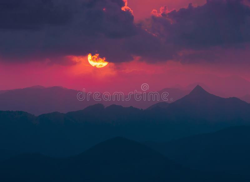 Mörk bakgrund med solen och moln över avlägsna berg royaltyfri bild