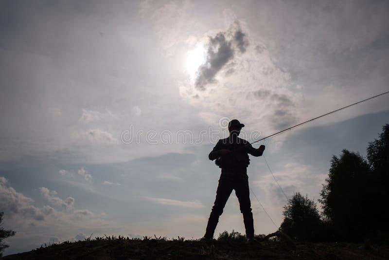 Mörk bild av fiskarestandsat kanten av vatten Han rymmer den klipska stången i hads Han fiskar Solen är bak molnet royaltyfria bilder