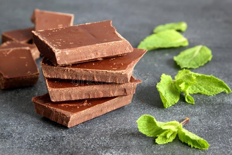 Mörk bitter choklad med få mintkaramellsidor på grå färger stiger ombord, närbilden royaltyfri bild