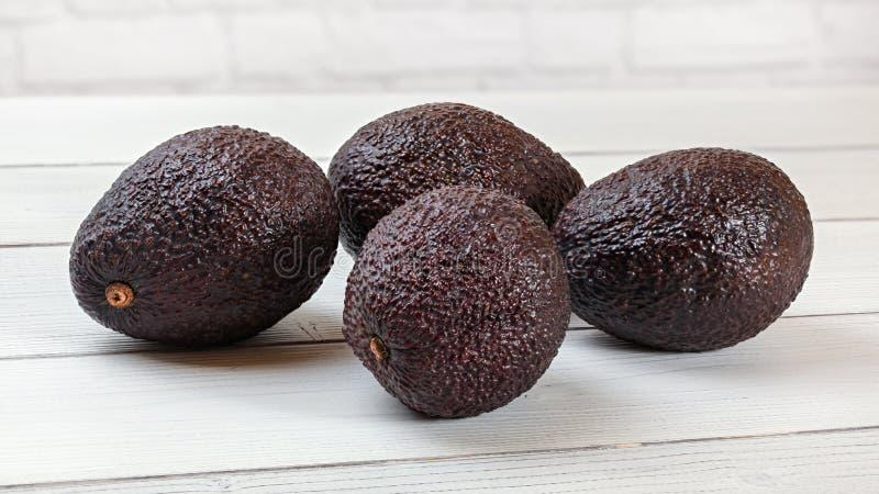Mörk brun avokadoBilse cultivar på skrivbordet för vita bräden arkivbild
