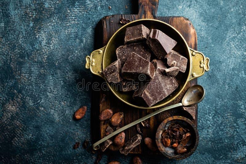 Mörk choklad lappar krossade och kakaobönor, kulinarisk bakgrund arkivfoton
