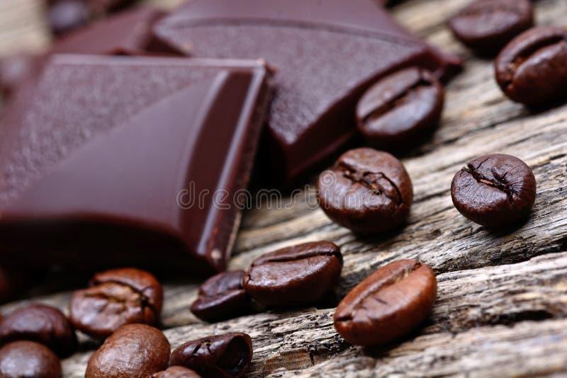 Mörk choklad med kaffebönor på trätabellen fotografering för bildbyråer