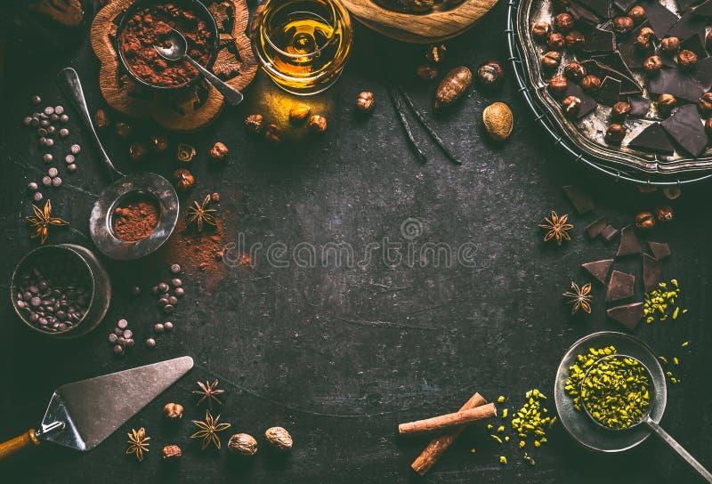 Mörk chokladbakgrund för konfekt eller bakelser med brutna krossade chokladstycken, kakaopulver, muttrar, kakaobönor, arkivbild