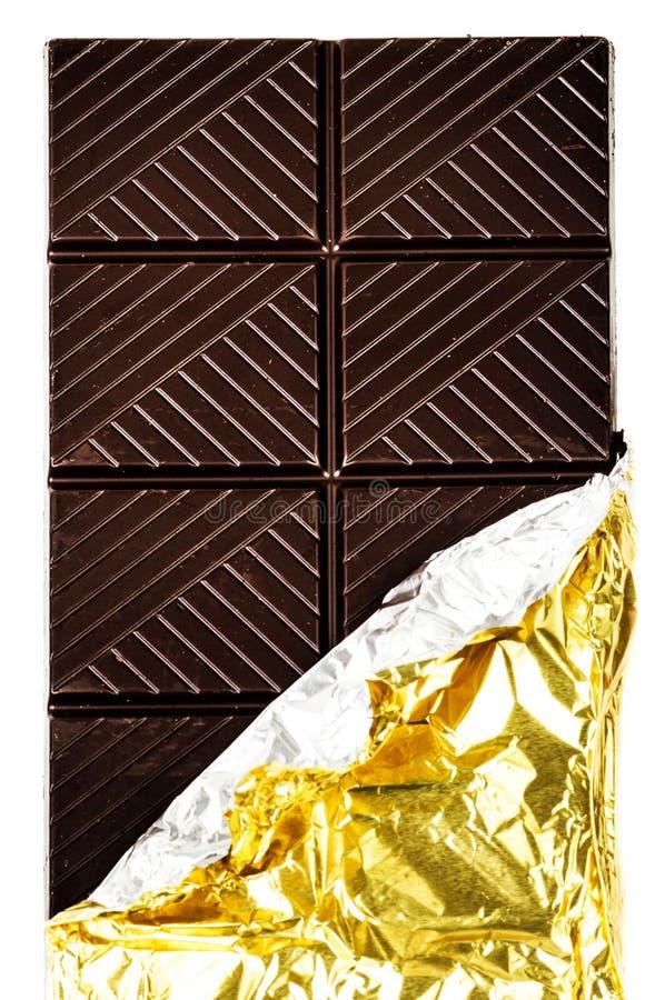 Mörk chokladstång i öppnad guld- folieinpackning som isoleras på wh royaltyfria bilder