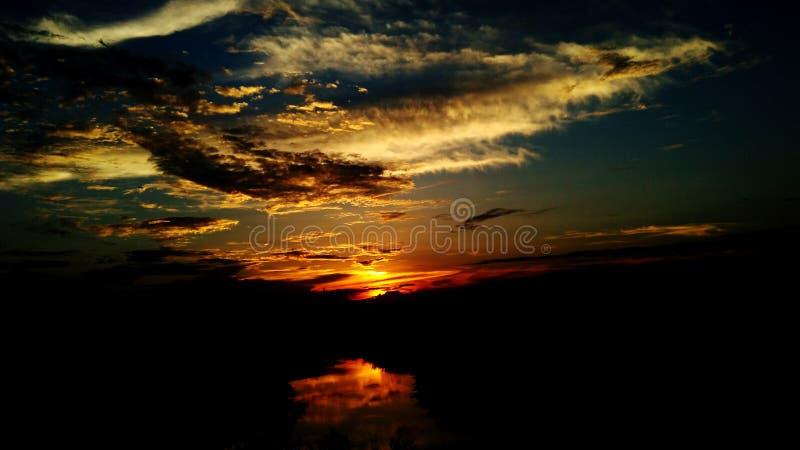 Mörk dramatisk solnedgångreflexion på floden royaltyfri foto