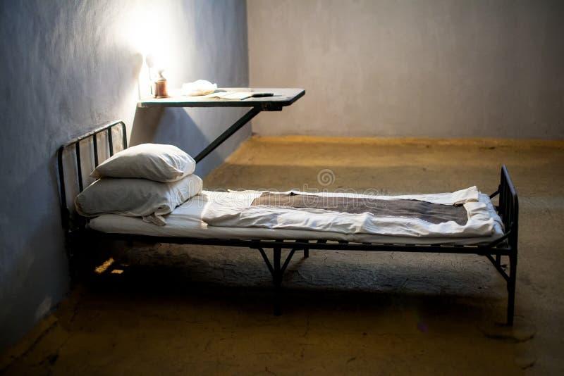 Mörk fängelsecell med säng royaltyfri fotografi