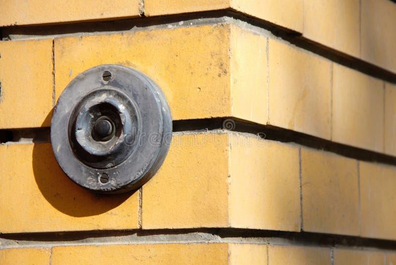 Mörk gammal metallisk ringklocka på tegelstenväggen arkivfoto