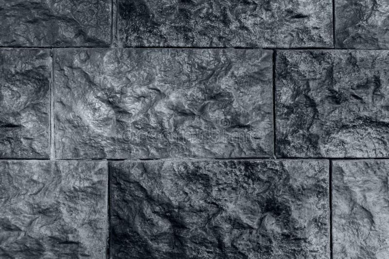 Mörk grå bakgrund, vägg från lättnadstegelsten royaltyfri fotografi