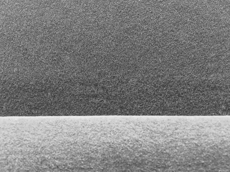 Mörk grå klädd med filt tygtextur med ljust - grå kantbakgrund arkivfoton