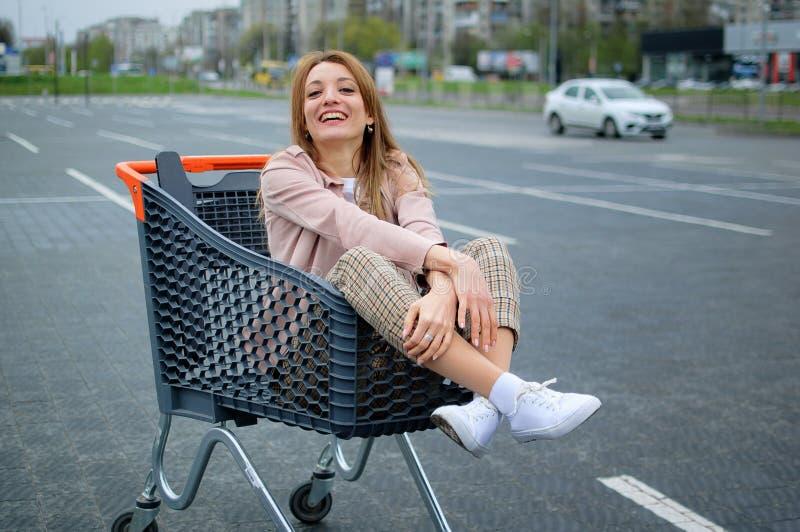 Mörk grå och orange shoppa vagn med den härliga flickan inom att stå i parkeringsplatsen av supermarket arkivfoto