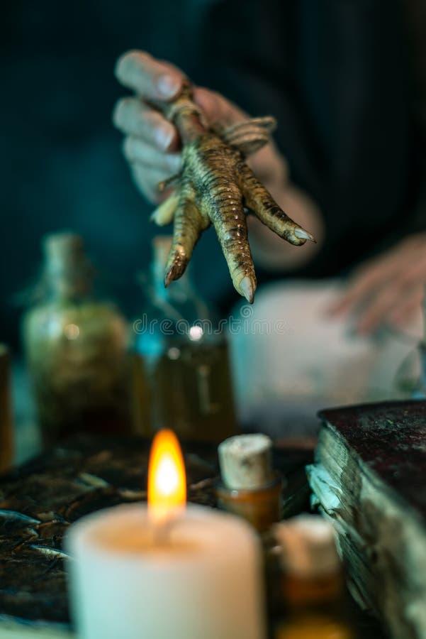 Mörk häxa på arbete: den svarta magiska kvinnan gör witcheryen, genom att blanda örter och att gjuta passen som kör magiska ritua arkivfoto