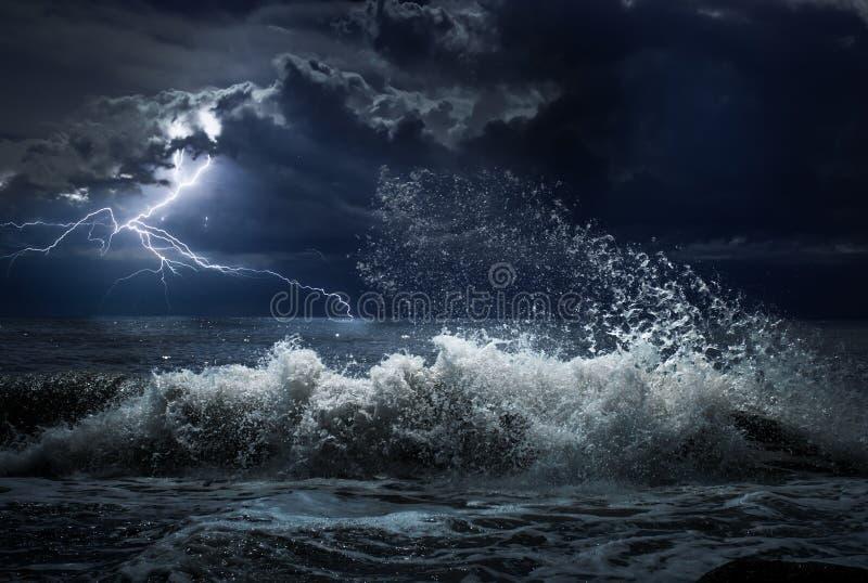Mörk havstorm med lgihting och vågor på natten arkivbilder
