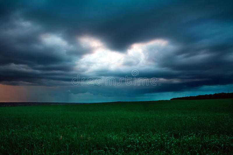 Mörk himmel med regnmoln över grönt fält arkivfoton