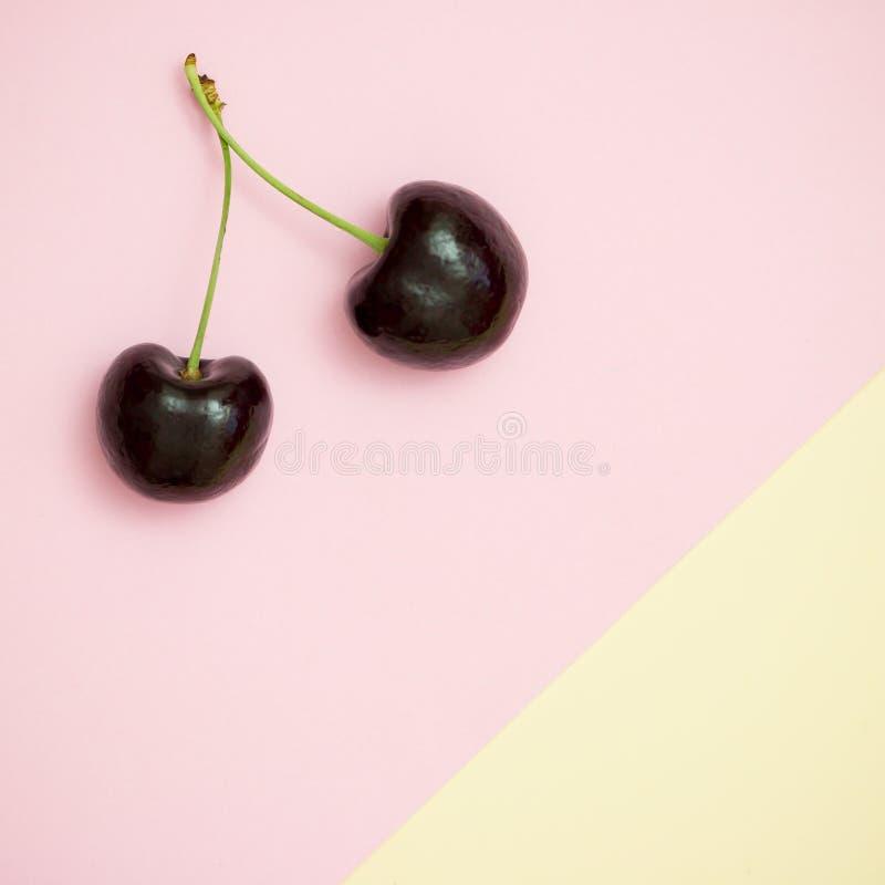 Mörk körsbär på pastellfärgad bakgrund royaltyfri bild