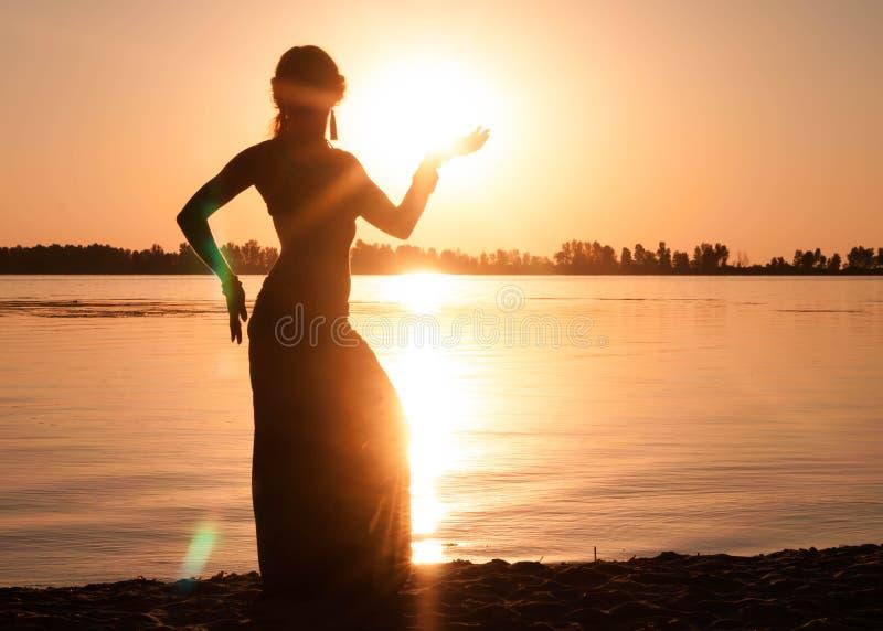 Mörk kontur av kvinnadansen som är trible nära flodkust arkivfoto