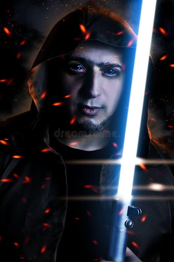 Mörk krigare med brun med huva udde som rymmer ett laser-svärd royaltyfri foto