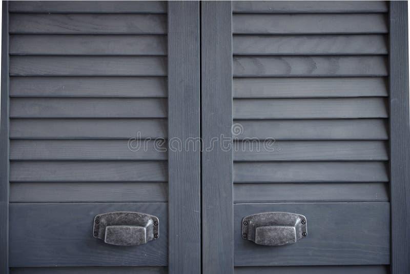 Mörk närbild - gråa slutaredörrar med slitna metallhandtag, skandinavisk minimalist kabinett inre, selektiv fokus arkivbild