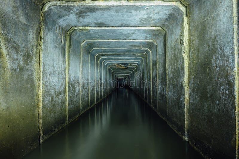 Mörk och kuslig översvämmad underjordisk avkloppbetongtunnel Flödande kast för industriellt avloppsvatten och för stads- kloak tu royaltyfria foton