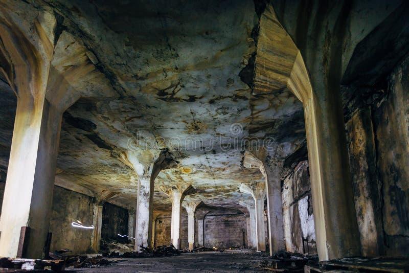 Mörk och kuslig inre av den underjordiska industriella korridoren på den övergav fabriken royaltyfri foto