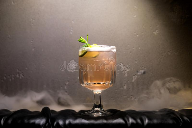 Mörk och stormig romcoctail med limefrukt mot bakgrund av smoen fotografering för bildbyråer