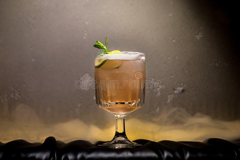 Mörk och stormig romcoctail med limefrukt mot bakgrund av smoen arkivfoton
