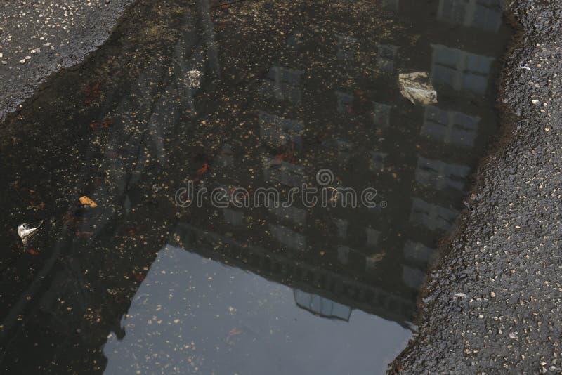 Mörk pöl i Asphalt Road med reflexion av kontorsbyggnad fotografering för bildbyråer