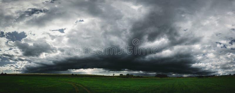 Mörk panorama för stormmoln ovanför fältet för grönt gräs arkivfoto